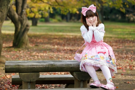 lolita: Japanese in sweet lolita cosplay sitting on a bench in Harajuku park, Tokyo