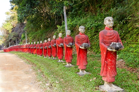 KA: Buddhist monks stone statues row at Ka Thawng cave, Hpa-an, Myanmar