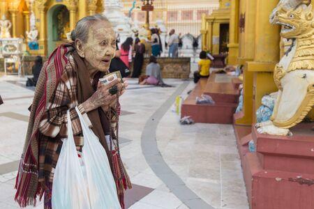 third world: RANGOON, MYANMAR - JANUARY 18, 2017 : An elderly woman is praying Buddha at the Shwedagon pagoda in Rangoon (Yangon), Myanmar