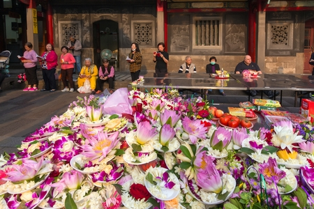 devotee: TAIPEI, TAIWAN - MARCH 28, 2017 : Tons of orchid and lotus flowers offerings and people praying at the Lungshan Buddhist temple in Taipei, Taiwan