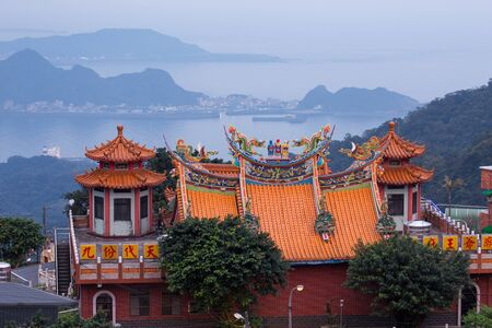 Dusk scenery in Jiufen town, the temple on the hill over the misty ocean, Taiwan