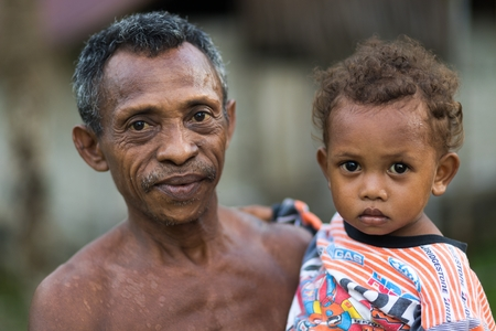 TUNGU VILLAGE, ARU ISLANDS, INDONESIA, DECEMBER 06, 2017 : Proud sweet father and daughter posing in the Tungu village, Aru islands, Papua, Indonesia.