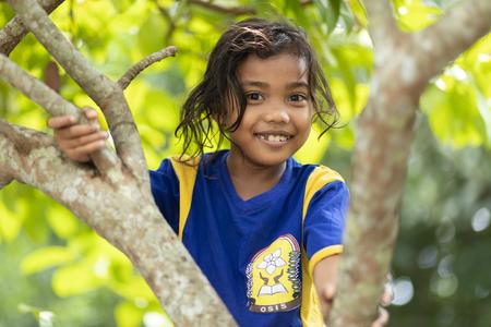 BANDA NEIRA, MALUKU ISLANDS, INDONESIA, DECEMBER 17, 2017 : Portrait of a smiling sweet little girl climbing at a tree in Banda Neira, Maluku islands, Indonesia. 新闻类图片