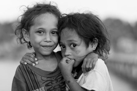 TUNGU VILLAGE, ARU ISLANDS, INDONESIA, DECEMBER 06, 2017 : Black and white portrait of two sisters in the Tungu village, Aru islands, Papua, Indonesia. 新聞圖片