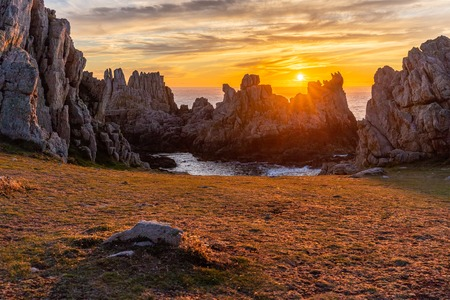 Bright warm susnet behind the sharp rocks of the Ushant island, Brittany, France