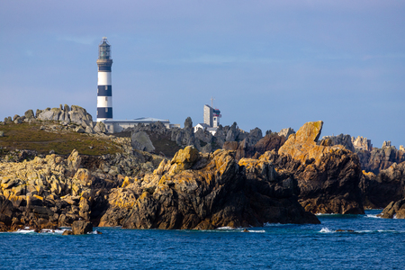 The Creach lighthouse on the sharp and rocky coastline of the Ushant island, Brittany, France Standard-Bild - 110918925