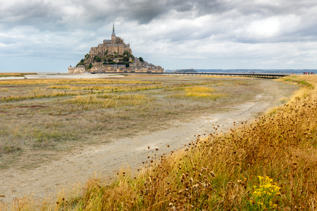 The Mont Saint Michel fortified village and church at low tide in end of summer under a dramatic sky, Normandie, France