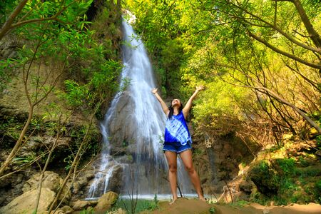 Happy woman outstretching her arms at the Thi Lo Su waterfall in Thailand Banco de Imagens