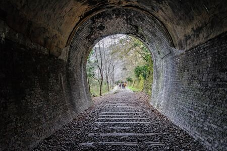 Old stone railway tunnel in the Osaka area ans trekkers walking on the path, Japan Banco de Imagens - 130115690