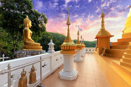 Golden Buddha statue and pagoda of the Wat Phra That In Kwaen temple , Phrae province, Thailand Stock Photo - 130115695