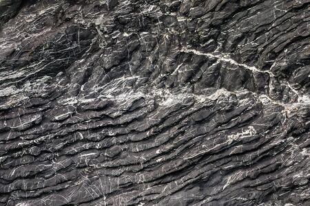 Dark granite stone along a tropical shore in Thailand Imagens