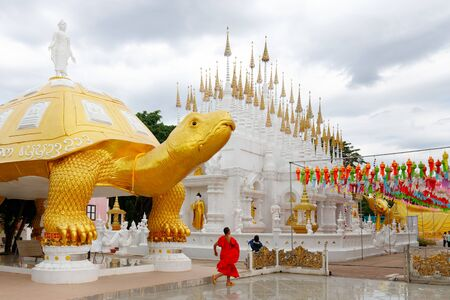 The Wat Phong Sunan Buddhist temple in Thailand, with a monk running under the giant turtle gilded statue. Stockfoto