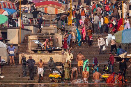 VARANASI, INDIA, 18 de enero de 2019: baño tradicional en el río Ganges y ritual hindú al amanecer a lo largo de los Ghats de Varanasi