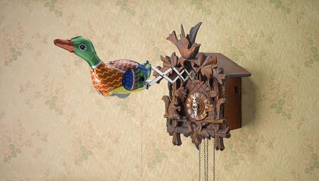 reloj cucu: Pato de juguete de la lata que sale del reloj de cuco contra el papel pintado florido