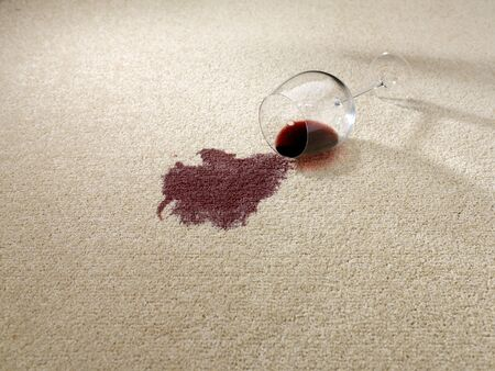 Spilt red wine from wine glass on carpet