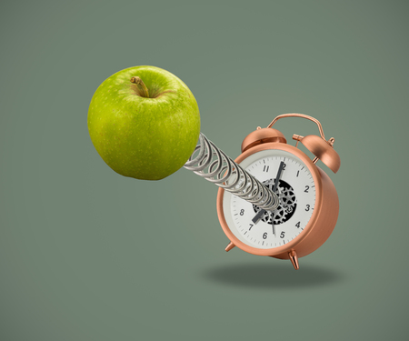 Apple on spring coming out of alarm clock on green background Banco de Imagens