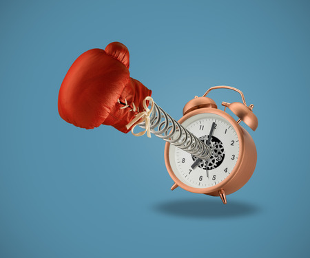 Red boxing glove springing out of alarm clock on blue background Stock Photo