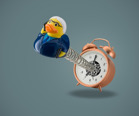 rubber duck business man springing out of alarm clock on blue background