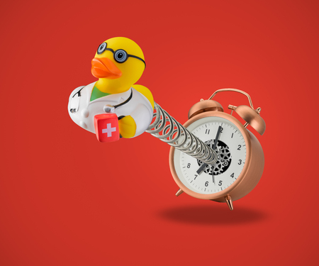 Rubber duck doctor coming out of alarm clock on spring on red background Stock Photo