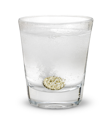 Pound coin like alka seltzer dissolving in glass isolated on white with drop shadow