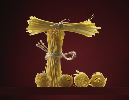 Dried pasta in the shape of an E against red background