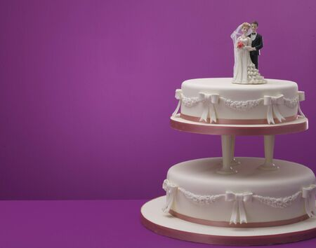 topper: Wedding cake with husband and wife topper against colored background