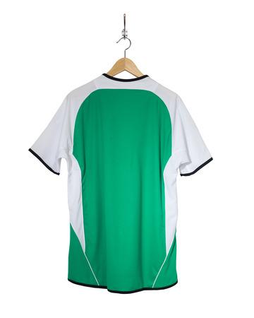 Camisa verde del fútbol que cuelga en el gancho y aislado en el fondo blanco Foto de archivo - 85368181