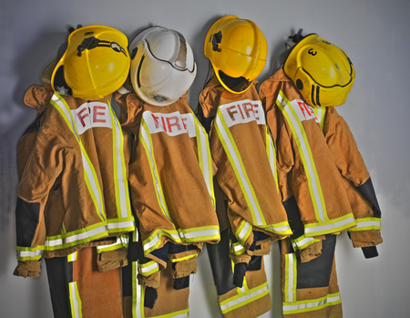 Fire suits hanging on wall in locker room