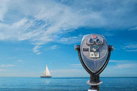 Binocular viewer overlooking ocean with yacht on horizon Stockfoto