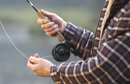Close up on hands fishing rod and reel