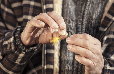 Close up on hands tying fly on line