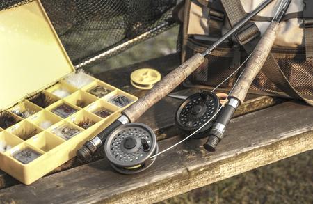 Fishing tackle rods net fly box on wooden bench Reklamní fotografie