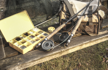 Fishing tackle rods net fly box on wooden bench Stockfoto