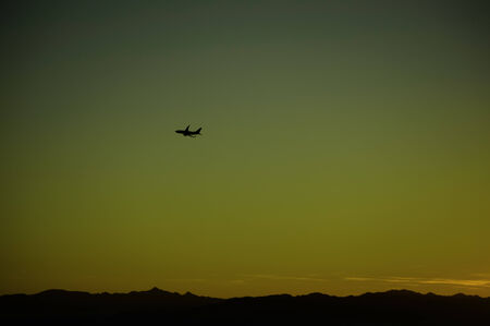 uncluttered: Jet plane taking off into the sunrise over distant mountains