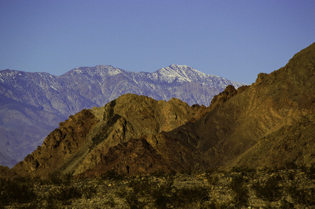 snow capped mountain: Warm colors of desert mountains contrast against the cold distant snow capped mountain range Stock Photo