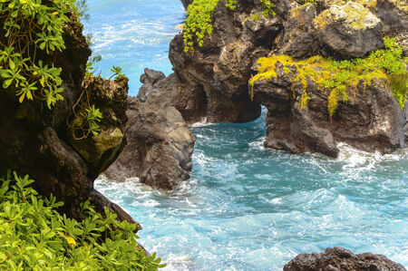 geen: The volcanic roack contrasts the lush geen and blue water on the Maui east coast near Hana