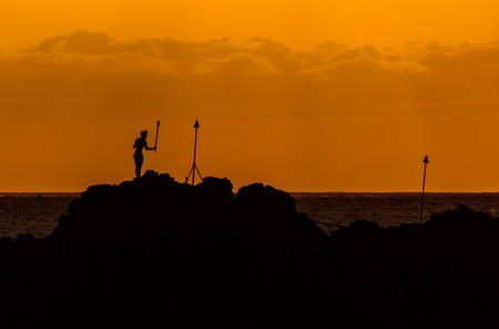 A cliff diver performs the torch lighting ceremony at Maui Blackrock photo