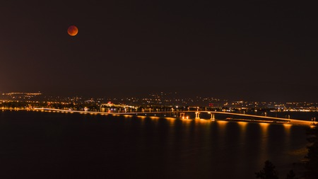 penumbra: A view of the bridge over Okanagan Lake between West Kelowna and Kelowna Brititsh Columbia Canada at night with a full moon during the lunar eclipse. September 27 2015