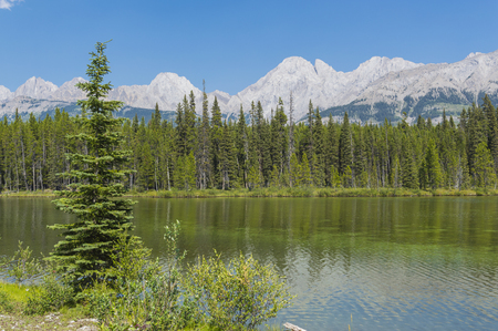 canmore: A small mountain lake on a summer day with mountains in the Rocky Mountains Kananaskis Country Alberta Canada