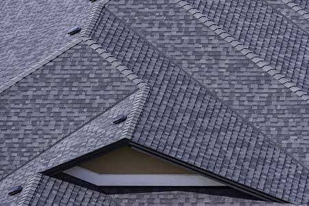 Dach w nowo wybudowanym osiedlu w Kelowna w Kolumbii Brytyjskiej w Kanadzie, na którym widać dachówki asfaltowe i wiele linii dachowych Zdjęcie Seryjne