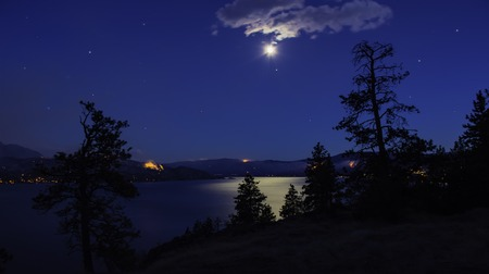 Night view of Okanagan Lake near Peachland and Kelowna British Columbia Canada in the moon light with many forest fires burning in the background