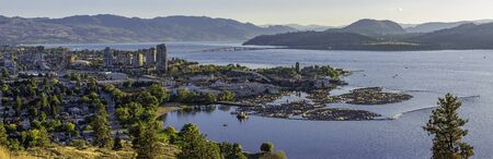 A high resolution panorama of the Kelowna British Columbia skyline and Okanagan Lake with the R W Bennett Bridge in the background, from Knox Mountain at sunset