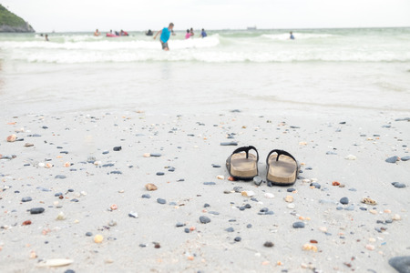 flip flops: Take off your shoes at the beach and go swimming in the sea Stock Photo