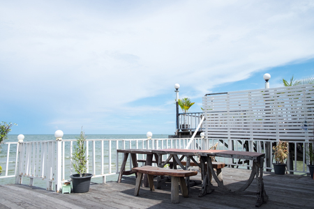 Tables and chairs on the porch that extends forward into the sea