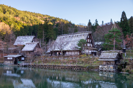 the sloped-roof and thatched-roof houses of snow cover and started to melt at Hida Folk Village, Japan