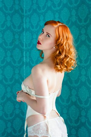 sexy redhead: Young and sexy redhead woman in white lingerie on blue retro background