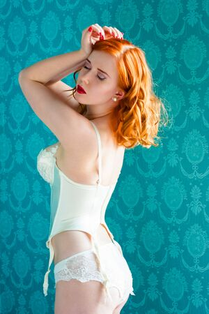 redhead lingerie: Young and sexy redhead woman in white lingerie on blue retro background