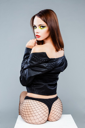Sexy seductive brunette female fashion model with bright make up posing in studio. Bright Colors. Sexy woman in a leather jacket. Female legs in black fishnet stockings