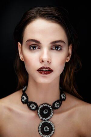 Jolie brunette femme face modèle posant en studio avec un collier