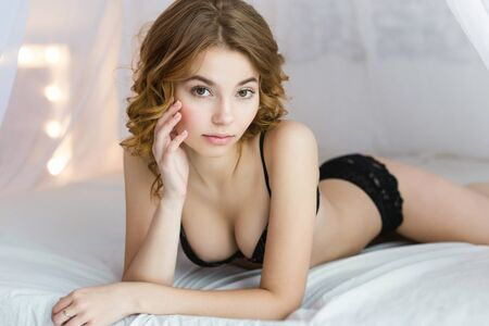 sensually: Portrait of young beautiful attractive lady wearing black bra and sensually looking at camera